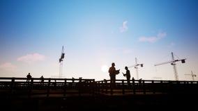 Coordenadores de construção nos esquemas da discussão com trabalhadores e silhueta ilustração stock