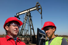 Coordenadores do petróleo que olham o laptop Imagem de Stock