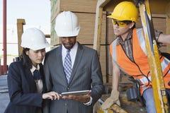 Coordenadores e trabalhador industrial fêmea que olham o PC da tabuleta Fotografia de Stock