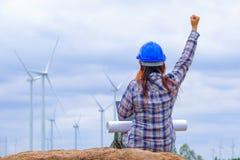 Coordenadores fêmeas felizes com o desenvolvimento das energias eólicas gerar a eletricidade foto de stock