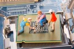 Coordenadores ou trabalhadores diminutos do técnico que reparam o processador central no cartão-matriz Servço informático e conce fotos de stock royalty free