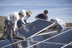 Coordenadores que colocam os painéis solares no telhado Foto de Stock Royalty Free