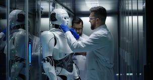 Coordenadores que testam em controles do robô dentro do laboratório imagens de stock royalty free