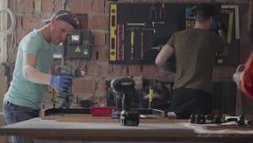 Coordenadores Tattooed dos mestres que fazem medidas, furando e trabalhando com construção no fundo de pequeno video estoque