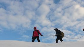 Coordinated teamwork, tourism in the winter. go to victory. mountaineer follow each other along the snow ridge stock footage