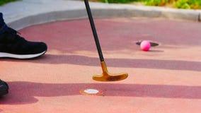 Coordonnée d'un putter de golf miniature peu de temps après piquer avec une boule de golf miniature rose à l'arrière-plan images stock
