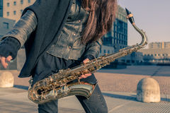 Coordonnée d'une jeune femme avec son saxophone Images libres de droits
