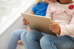 Coordonnée de deux filles s'asseyant sur des escaliers utilisant la Tablette de Digital Image libre de droits