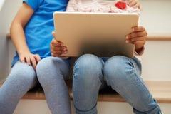Coordonnée de deux filles s'asseyant sur des escaliers utilisant la Tablette de Digital Photographie stock