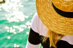 Coordonnée de femme détendant avec le chapeau de paille jaune sur la mer avec la réflexion du soleil le jour ensoleillé Image libre de droits