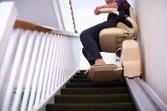 Coordonnée de femme supérieure s'asseyant sur l'ascenseur d'escalier à la maison pour aider la mobilité images libres de droits
