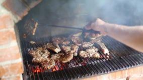 Coordonnées d'un homme faisant cuire la viande sur un gril de barbecue clips vidéos