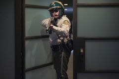 Cop Aiming Rifle While Standing At Door Royalty Free Stock Photo