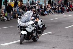 Cop bij fiets het berijden onderaan de straat stock foto