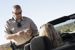 Cop Checking Woman's License Stock Photos
