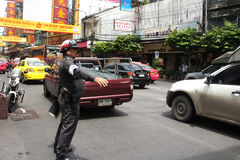 Cop commanding traffic in Chinatown, Bangkok Stock Photos