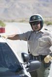 Cop die zich door Zijn Auto bevinden Stock Foto