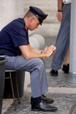 Cop on his cell phone sitting Stock Photography