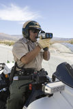 Cop Monitoring Speed Though Radar Gun Stock Photography