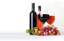 Copa, botellas de vino y uvas imagen de archivo
