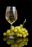 Copa con el vino blanco y las uvas en un fondo negro Fotos de archivo libres de regalías