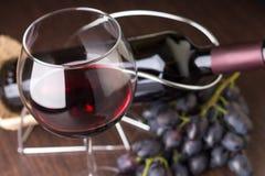 Copa con el vino con las uvas y la botella en el fondo Imágenes de archivo libres de regalías