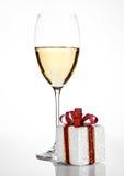 Copa de vino blanca con la caja de regalo de la Navidad Imagen de archivo libre de regalías