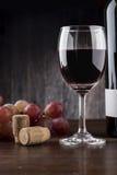 Copa de vino, botella y uvas en un fondo de madera Imágenes de archivo libres de regalías