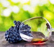 Copa de vino con la uva en la tabla de madera Fotos de archivo