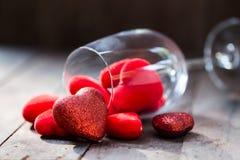 Copa de vino con los corazones rojos el día de tarjeta del día de San Valentín Foto de archivo
