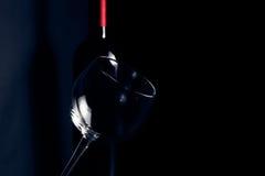 Copa de vino delante de la botella cerca de su sombra en luz azul marino Imagen de archivo libre de regalías