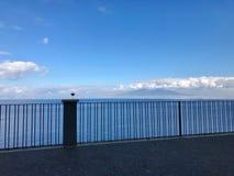 Copa de vino en una verja que pasa por alto el mar Imagen de archivo