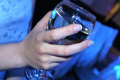 Copa de vino hermosa a disposición en un fondo azul imagenes de archivo