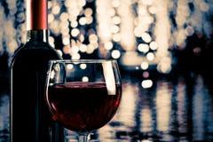 Copa de vino roja cerca de la botella con el bokeh ligero Fotografía de archivo