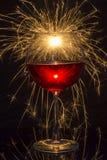 Copa de vino roja con la bengala Imagenes de archivo
