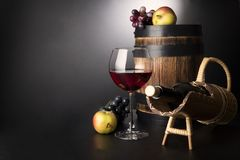 Copa de vino roja con la botella en el apoyo del sraw y el barril de madera viejo rodeados por las frutas: vid y manzanas Fotos de archivo