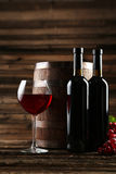 Copa de vino roja con la botella y barril en el fondo de madera marrón Imagenes de archivo