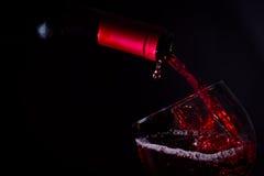 Copa de vino roja de colada en luz oscura Imágenes de archivo libres de regalías