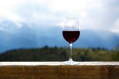 Copa de vino roja en una comida campestre que se coloca en una tabla de madera delante del fondo hermoso de la montaña Fotos de archivo libres de regalías