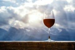Copa de vino roja en una comida campestre que se coloca en una tabla de madera delante del fondo hermoso de la montaña Foto de archivo libre de regalías