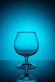Copa de vino vacía en un fondo azul imagen de archivo libre de regalías