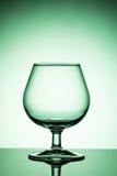 Copa de vino vacía en un fondo verde imagen de archivo