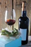 Copa de vino y botella con el regalo en fondo de madera Imagen de archivo
