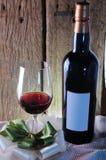 Copa de vino y botella con la cinta en fondo de madera Fotografía de archivo