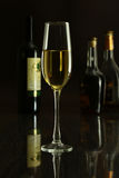 Copa de vino y botella en un fondo negro del espejo Foto de archivo libre de regalías