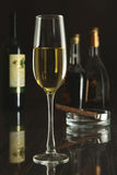 Copa de vino y botella en un fondo negro del espejo Imagenes de archivo