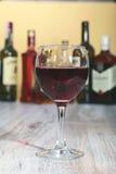 Copa de vino y botella en un fondo negro del espejo Fotos de archivo