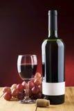 Copa de vino y botella en una tabla de madera sobre el fondo rojo Imágenes de archivo libres de regalías