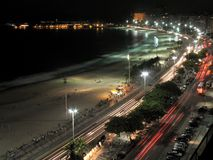 Copacabana by Night - 1. Headlights and taillights leave streaks on Copacabana Beach's esplanade on a warm summer night, with pedestrians enjoying the beach royalty free stock photos
