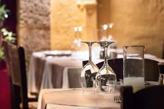 Copas de vino al revés en una tabla con las coctelera, las placas y los cubiertos en la tarde, al aire libre foto de archivo